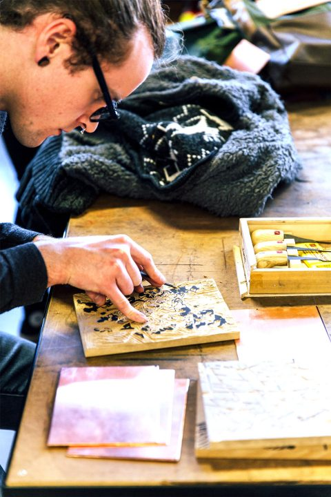 Male student etches a design into a wood block during a print making class.