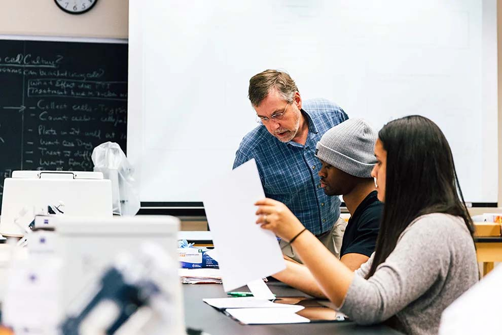 Male professor answers questions from a male and female student sitting at a lab table in a biology classroom.