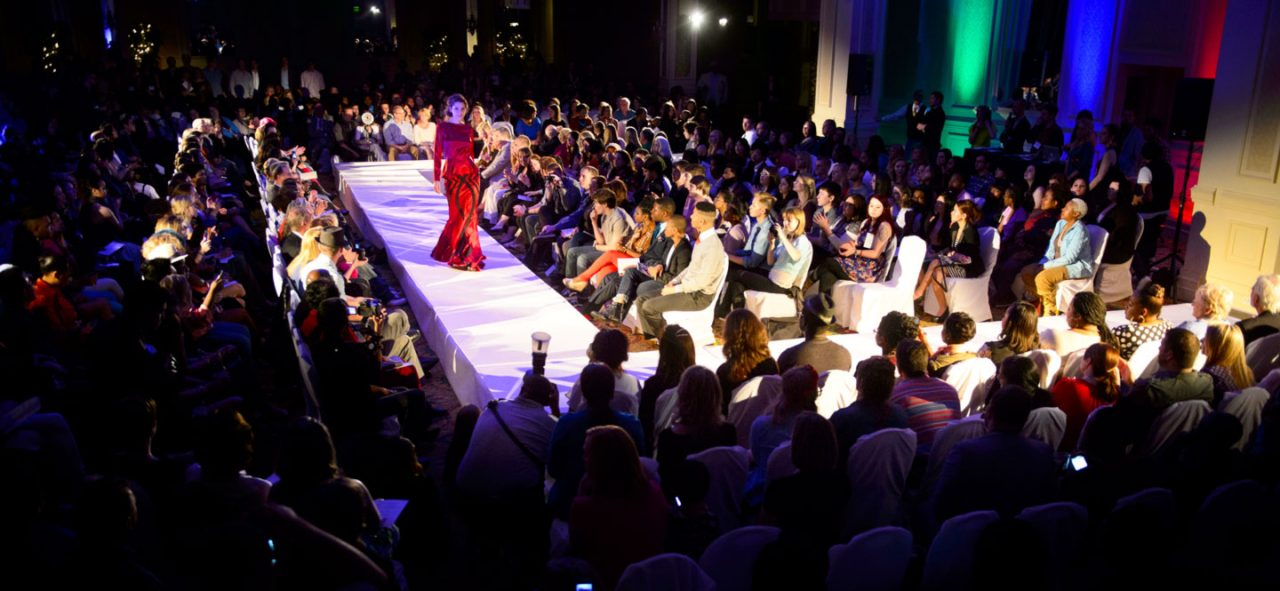 Female student wearing an evening gown walks down white fashion runway surrounded by spectators.