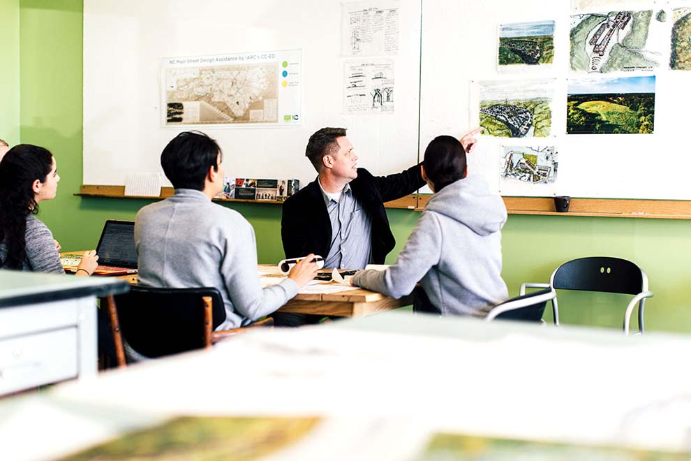 Male architect reviews blueprints and sketches with a group of students gathered around a table.