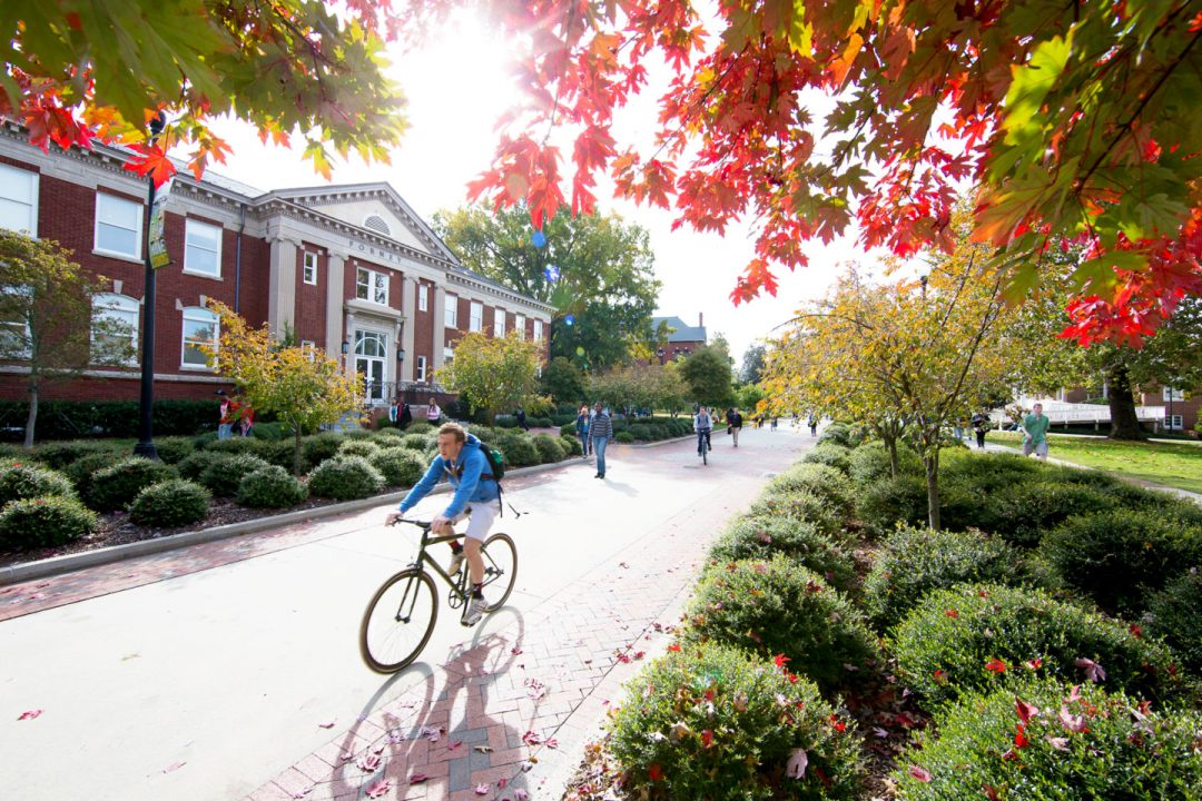 Male student rides a bike past a historic building on a brick paved pathway.