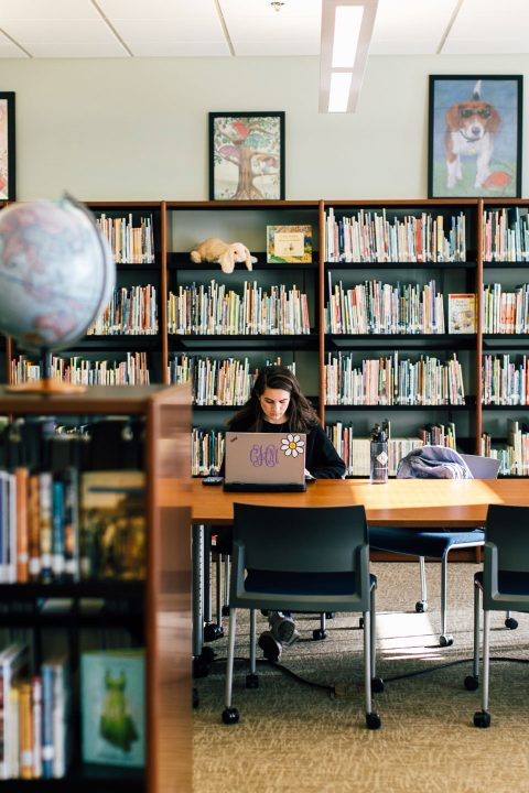Female student works at a laptop surrounded by bookshelves