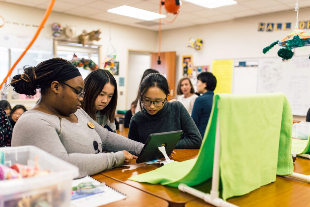Three female students observe augmented reality app on a tablet screen positioned in front of a green screen.