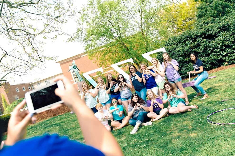 Group of female students in a sorority pose together for a photo in front of large greek letters on the campus lawn.