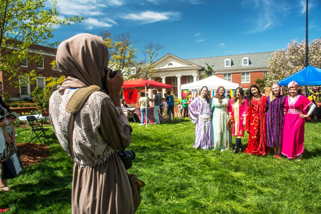 Female student takes a picture of a group of other female students wearing traditional cultural clothing