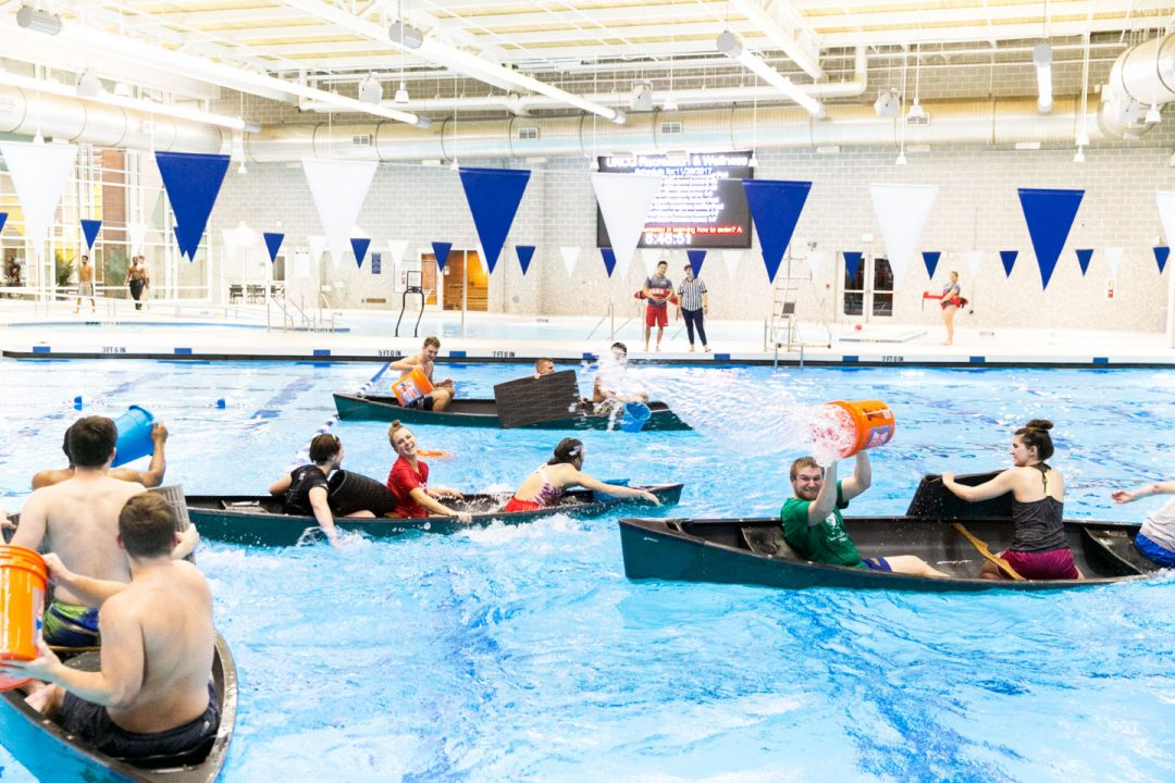 Students sit in canoes in an indoor swimming pool, throwing buckets of water into each other's boats.