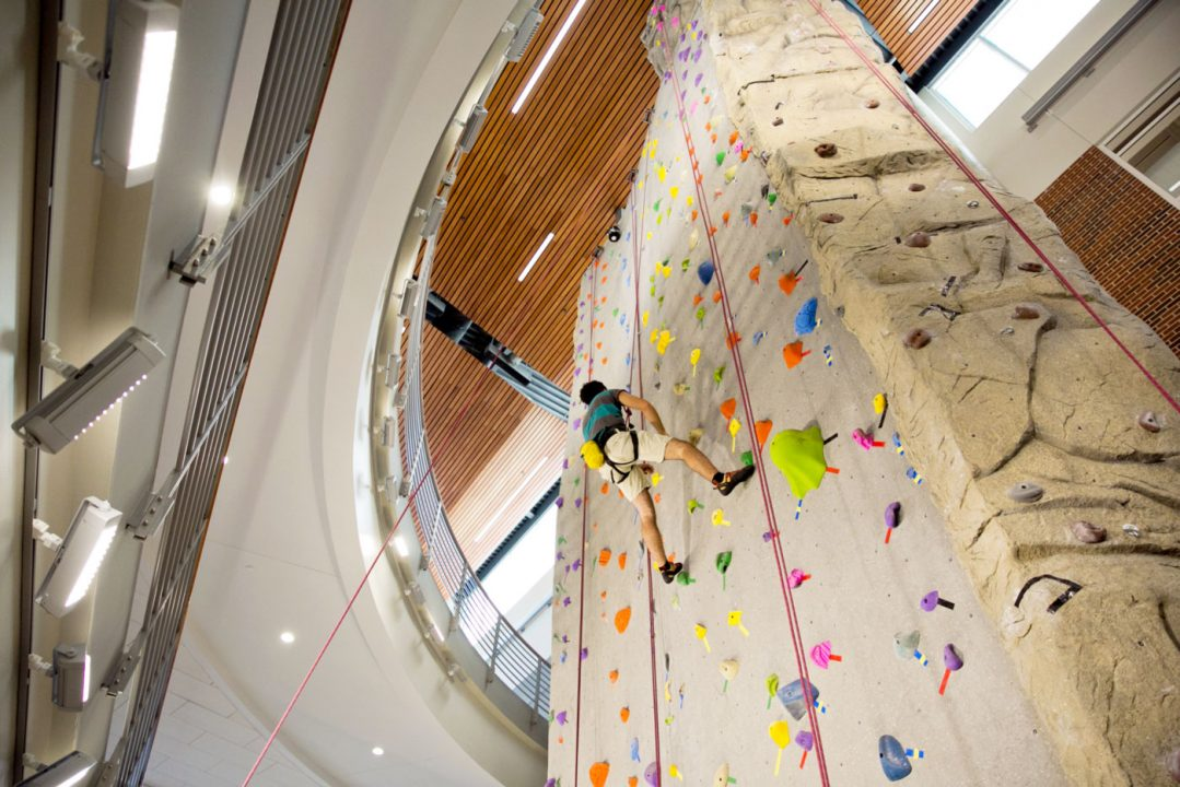 Student scales a rock wall that extends all the way to a high ceiling.