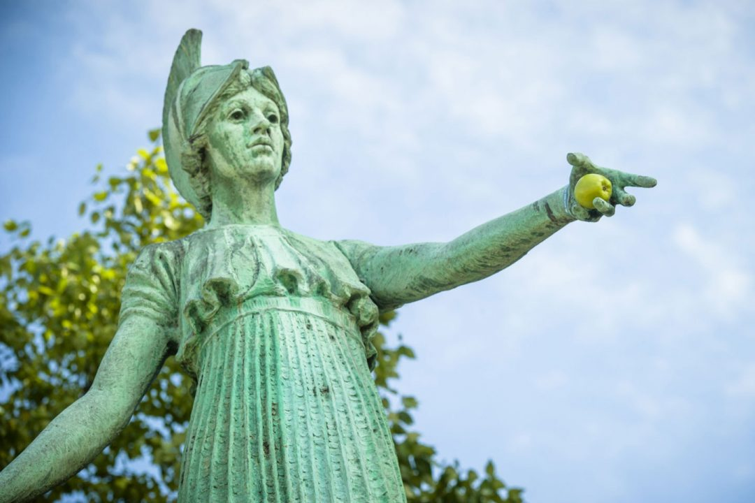 Copper Minerva statue with apple placed into the hand of her outstretched arm.