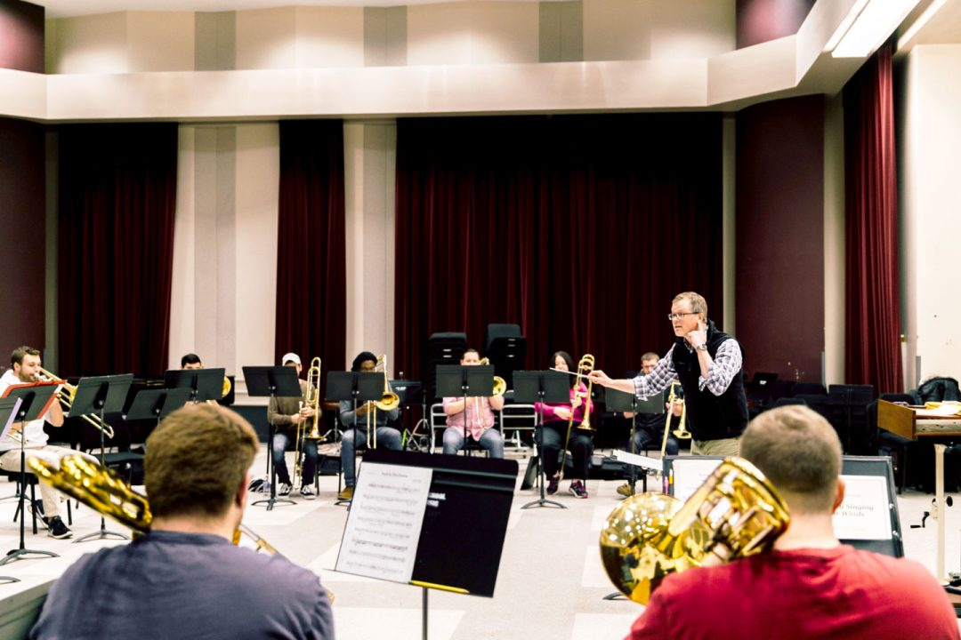 Music professor conducts a group of music students practicing a piece for a trombone ensemble.