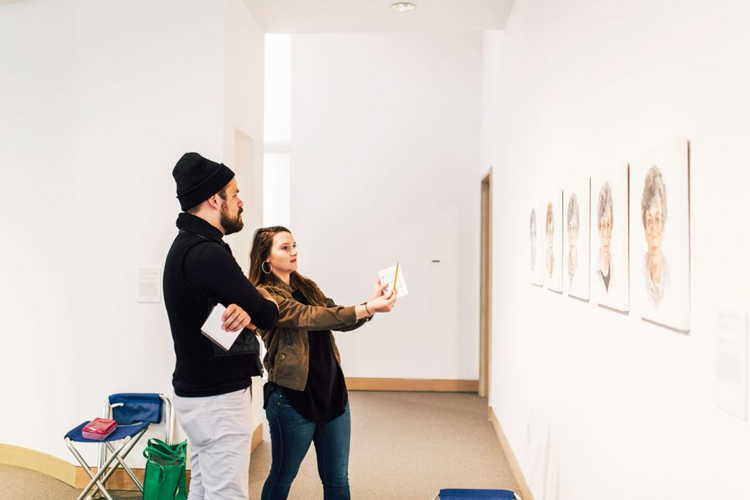A male and female student discuss a series of paintings hanging on the wall
