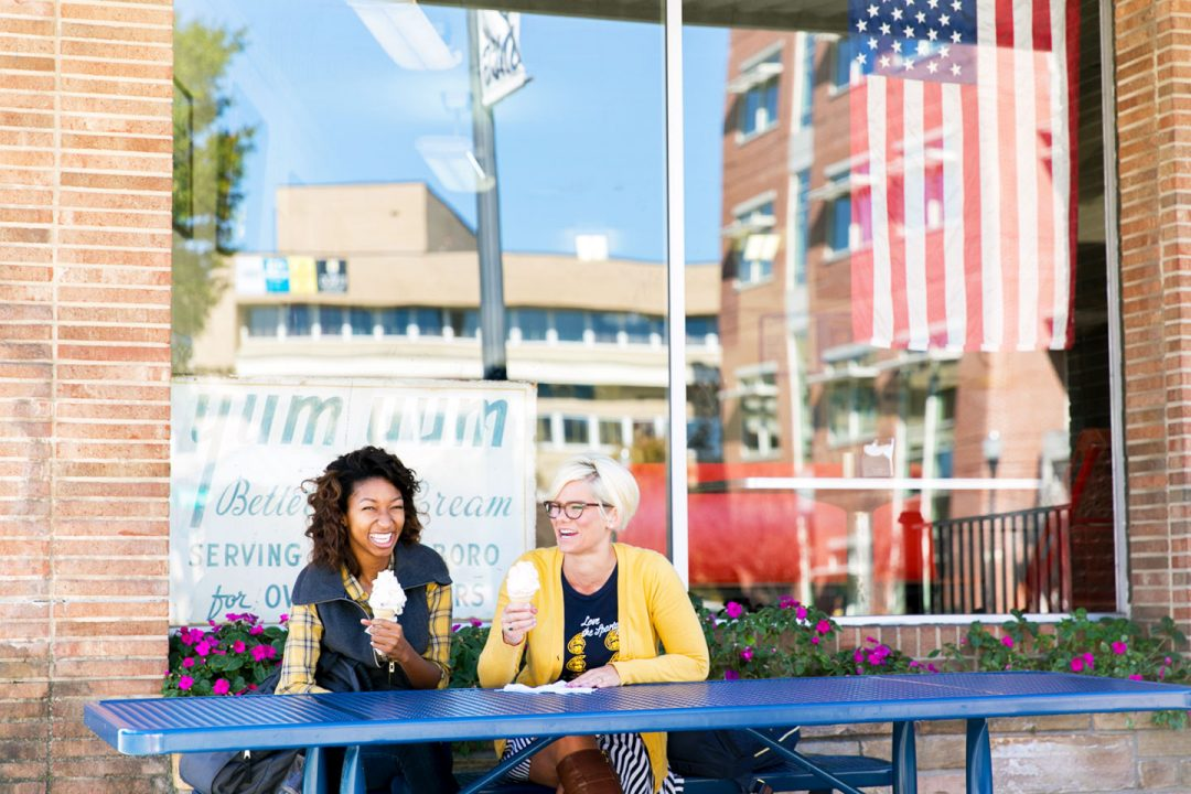 Two female students eat ice cream cones at a picnic bench in front of an ice cream shop