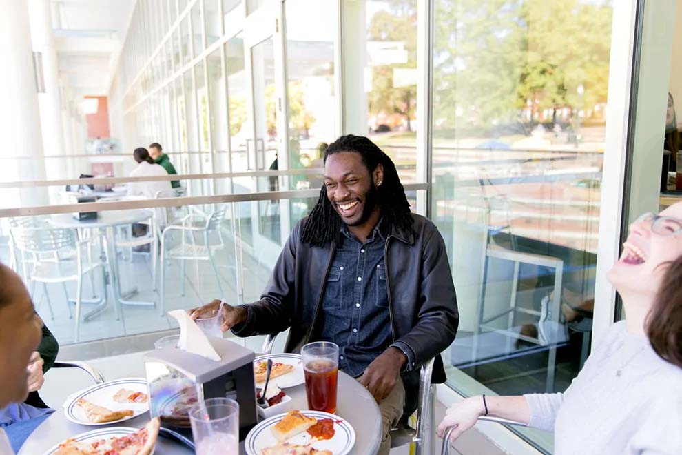 A male student laughs with friends while eating pizza at the dining hall.