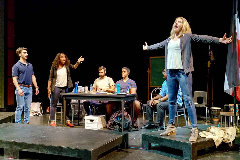 Diverse ensemble of male and female students performs a play on stage